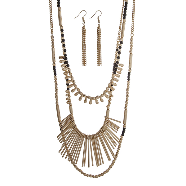 Wholesale gold layering necklace set displaying black gold beads metal fringe