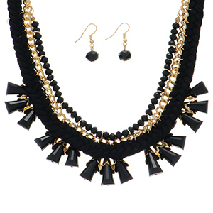 "18"" Gold tone necklace featuring a black tone braided thread focal accented by faceted round and cylinder shaped beads with matching 1"" fishhook style earrings."