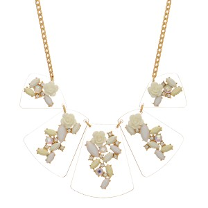 "Gold tone necklace featuring clear wedges with white flower and stone decor. Approximately 18"" in length."