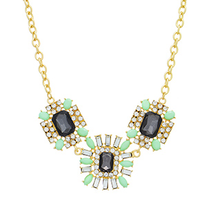 "Gold tone necklace featuring three black cabochons surrounded by clear rhinestones and mint green stones. Approximately 14"" in length."