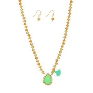 "Gold tone necklace set featuring sage green  beads with a mint green teardrop shaped cabochon and tassel accent. Approximately 15"" in length."