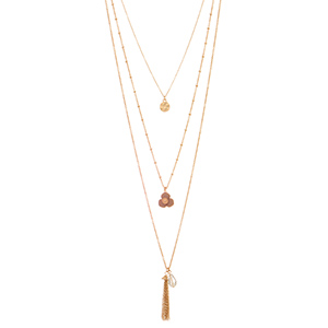 "Gold tone layering necklace featuring a hammered disk, brown flower, and a metal tassel with clear bead decor. Approximately 28"" in length."