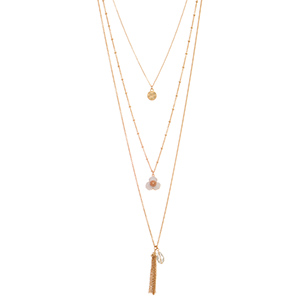"Gold tone layering necklace featuring a hammered disk, white flower, and a metal tassel with clear bead decor. Approximately 28"" in length."