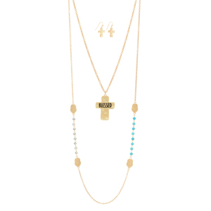 "Worn gold tone layering necklace featuring turquoise and gray beads with cross stations and a hammered cross stamped ""BLESSED"". Approximately 35"" in length."