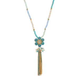 "Gold tone necklace featuring turquoise, blue, and ivory beads and a turquoise chain link flower with a cluster of beads and metal tassel. Approximately 32"" in length."