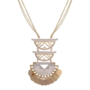 "Gold tone necklace featuring a two tone Aztec inspired pendant with dangling disk. Approximately 27"" in length."