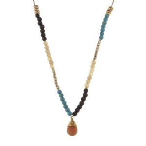 "Worn gold tone half beaded necklace with dark brown wood, beige, and turquoise beads and a wire wrapped peach natural stone. Approximately 34"" in length."
