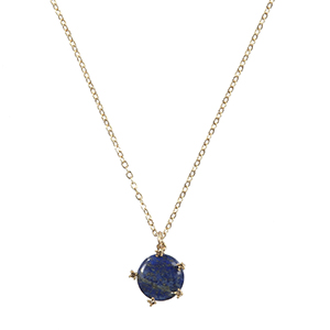 "Worn gold tone necklace with a small round lapis stone pendant. Approximately 16"" in length."