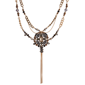 "Gold tone double stranded necklace displaying a gray and champagne rhinestone focal with a chain tassel surrounded by black and brown beads. Approximately 18"" in length."
