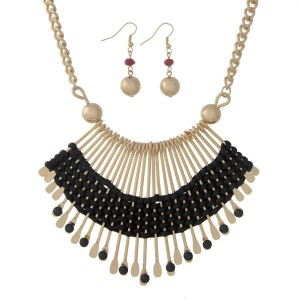 "Gold tone necklace set displaying a bohemian style casting wrapped with black cord. Approximately 16"" in length."