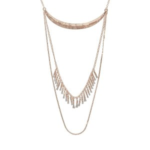 "Gold tone necklace displaying a hammered crescent with a chain drape and a chain with gray mini tassels. Approximately 29"" in length."