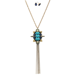 "Burnished gold tone necklace set displaying a pendant with turquoise and beige cabochons, blue rhinestones, and a metal tassel. Approximately 29"" in length."