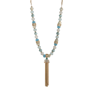 "Gold tone double strand necklace displaying blue and white beads with a chain tassel. Approximately 30"" in length."