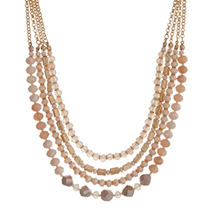 "Gold tone layering necklace displaying strands of ivory glass beads. Approximately 18"" in length."