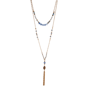 "Gold tone layering necklace displaying blue beads and a brown stone with a chain tassel. Approximately 28"" in length."