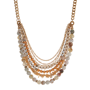 "Gold tone necklace displaying rows of ivory chipstone and peach and green beads. Approximately 18"" in length."