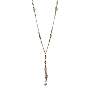 "Gold tone necklace displaying mint bead stations and a tassel with mini spikes. Approximately 30"" in length."