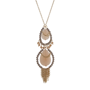 "Gold tone necklace displaying two peach teardrop shape stones surrounded by gray beads with chain fringe. Approximately 26"" in length."