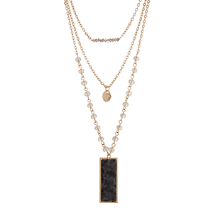 "Gold tone layering necklace displaying gray and white beads, a hammered disk, and a black natural stone pendant. Approximately 23"" in length."