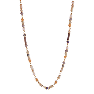 "Purple, ivory, and peach beaded necklace with gold tone disk accents. Approximately 36"" in length."