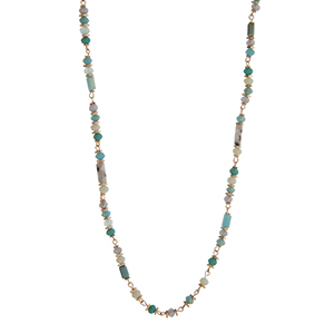 "Turquoise, mint, and gray beaded necklace with gold tone disk accents. Approximately 36"" in length."