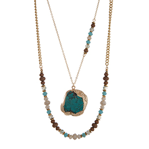 "Gold tone layering necklace displaying ivory, turquoise, and brown glass beads with a turquoise natural stone pendant. Approximately 21"" in length."
