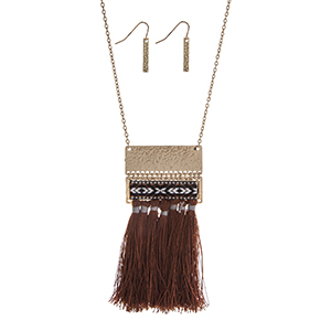 "Gold tone necklace set displaying a hammered pendant with a black, white, and brown tribal print thread and brown tassels. Approximately 28"" in length."