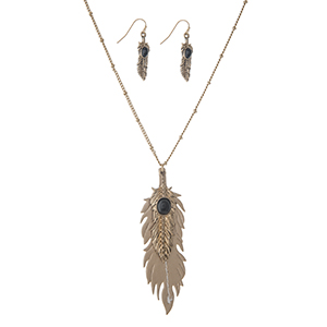 "Worn gold tone necklace set displaying a gold 3 1/2"" faux leather feather and a 2 1/4"" metal feather with a black stone focal. Approximately 27"" in length."