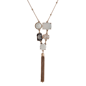"Gold tone necklace displaying multiple shaped opal, champagne, white, and black cabochons with a 2 1/4"" chain tassel. Approximately 29"" in length. Overall length 33 1/4""."