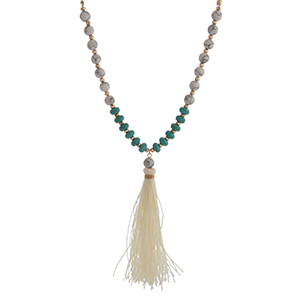 "Gold tone half beaded necklace displaying howlite and turquoise stone beads with a 3 1/2"" cream fabric tassel. Approximately 29"" in length."