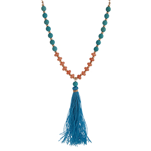 "Gold tone half beaded necklace displaying  turquoise and coral stone beads with a 3 1/2"" blue fabric tassel. Approximately 29"" in length."