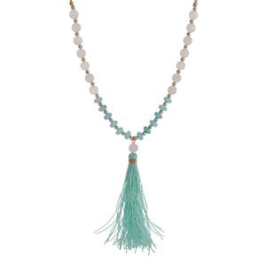 "Gold tone half beaded necklace displaying white and blue stone beads with a 3 1/2"" mint fabric tassel. Approximately 29"" in length."