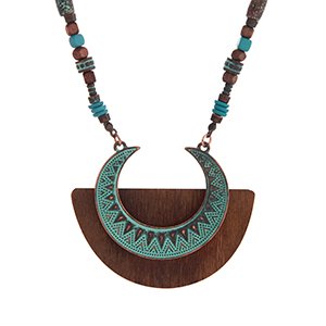 "Burnished copper tone bohemian style necklace with turquoise and patina beads and a crescent shaped pendant on brown wood. Approximately 29"" in length."