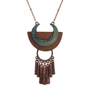 "Copper gold tone bohemian style necklace displaying a textured patina pendant on brown wood with metal fringe. Approximately 30"" in length."