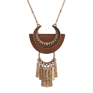 "Burnished gold tone bohemian style necklace displaying a textured pendant on brown wood with metal fringe. Approximately 30"" in length."