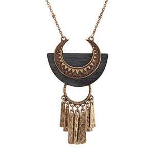 "Burnished gold tone bohemian style necklace displaying a textured pendant on gray wood with metal fringe. Approximately 30"" in length."