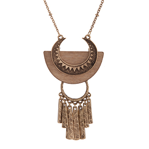 "Burnished gold tone bohemian style necklace displaying a textured pendant on light brown wood with metal fringe. Approximately 30"" in length."