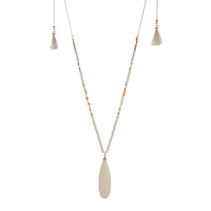 "Gold tone adjustable necklace displaying beige and white beads with a 2 1/4"" ivory teardrop shaped stone and two ivory mini tassels. Approximately 46"" in length."