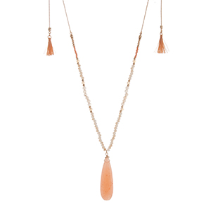"Gold tone adjustable necklace displaying beige beads with a 2 1/4"" peach teardrop shaped stone and two peach mini tassels. Approximately 46"" in length."