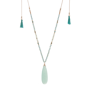 "Gold tone adjustable necklace displaying light blue beads with a 2 1/4"" mint teardrop shaped stone and two mint mini tassels. Approximately 46"" in length."