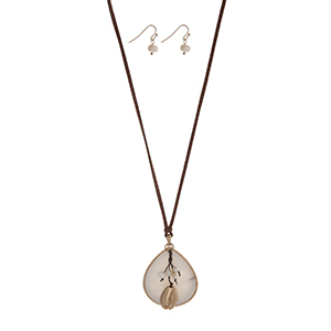 """Adjustable brown cord necklace set displaying a white teardrop shape pendant with a cluster of faux pearls and a gold tone cowry shell. Approximately 24"""" in length."""