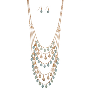 "Gold tone layering necklace set with rows of hammered and blue teardrop shapes. Approximately 30"" in length."