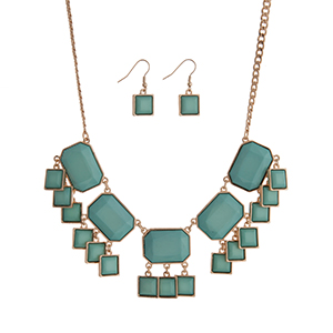 "Gold tone necklace set displaying mint green cabochons with dangling squares. Approximately 17"" in length."