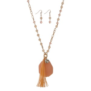"Gold tone necklace set displaying peach beads with a peach natural stone, a pave ball, and a  3"" fabric tassel. Approximately 36"" in length."