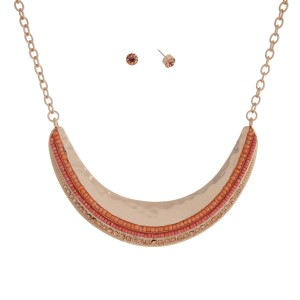 "Gold tone necklace set displaying a hammered crescent with peach and coral seed beads and peach rhinestones. Approximately 15"" in length."