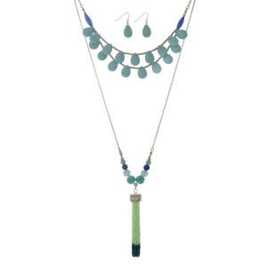 "Gold tone layering necklace set displaying turquoise teardrop shaped beads and a 3"" green and navy seed bead tassel. Approximately 32"" in length."