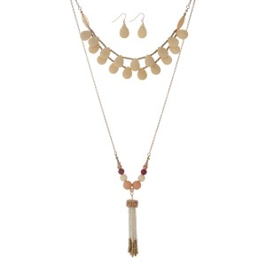 "Gold tone layering necklace set displaying cream teardrop shaped beads and a 3"" white and gold seed bead tassel. Approximately 32"" in length."