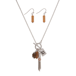 """Matte silver tone toggle necklace set with a brown stone, a topaz bead, a chain tassel, and a plate stamped """"True love"""". Approximately 16"""" in length."""