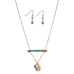 """Gold tone necklace set displaying a bar with turquoise beads and a hammered plate stamped """"Live fast Love hard"""". Approximately 17"""" in length."""