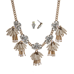 "Burnished gold tone necklace set displaying white opal rhinestones with dangling ivory beads. Approximately 17"" in length."